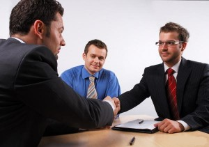 Job interview for administrative position , three people in a room, one canddiate and two interviewers. They are just shaking hands.