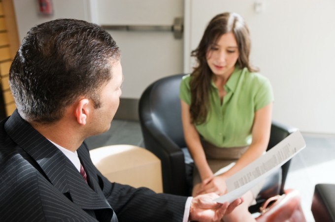 Interviewer and applicant discussing resume in an interview for administrative assistant position